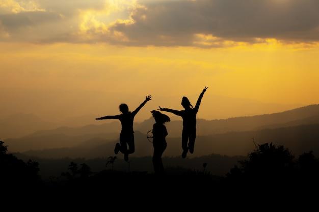 Grupo de pessoas felizes pulando na montanha ao pôr do sol