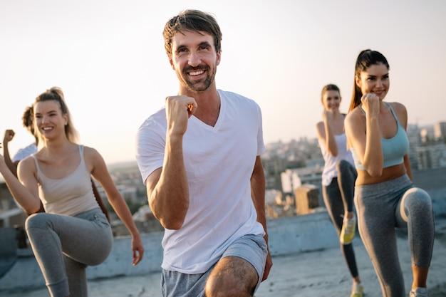 Grupo de pessoas felizes treinando ao ar livre no telhado