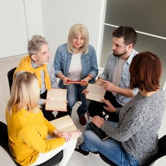 Grupo de pessoas lendo livros em sessão de terapia