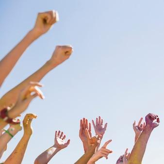 Grupo de pessoas levantando as mãos contra o céu azul, celebrando o holi