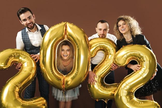Grupo de pessoas lindas e bem vestidas comemorando a chegada do ano novo de 2022 com balões dourados sobre fundo marrom