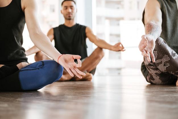Grupo de pessoas meditando na posição de lótus no estúdio