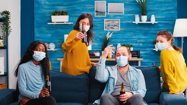 Grupo de pessoas mestiças com máscara protetora conversando com amigos remotos em uma nova festa normal na sala de estar
