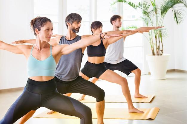 Grupo de pessoas, mulheres e homens durante a aula de ioga, em pé em uma fileira e fazendo a pose de ioga do guerreiro. retrato interno em sala de ginástica espaçosa e bem iluminada