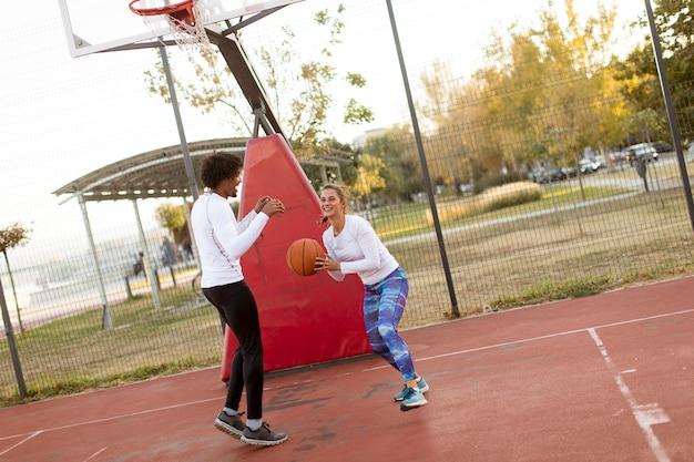 Grupo de pessoas multiétnicas jogando basquete na quadra
