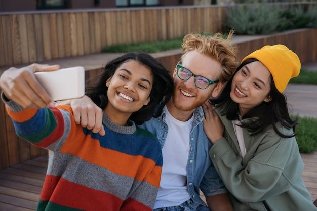 Grupo de pessoas multirraciais emocionais usando telefone celular e tirando selfies