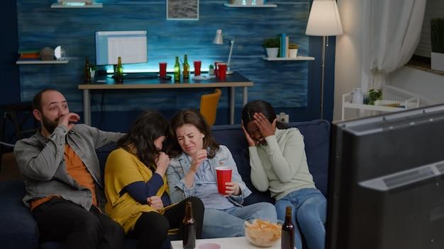 Grupo de pessoas multirraciais sentadas confortavelmente no sofá enquanto assistem a um filme de suspense