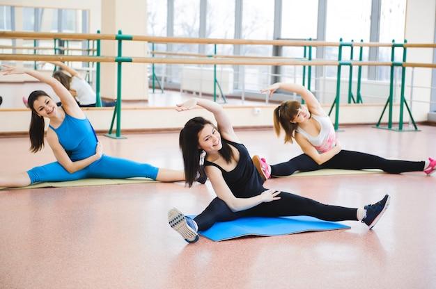 Grupo de pessoas no ginásio em uma aula de alongamento