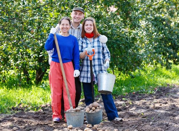 Grupo de pessoas no jardim com uma pá de balde plantando batatas