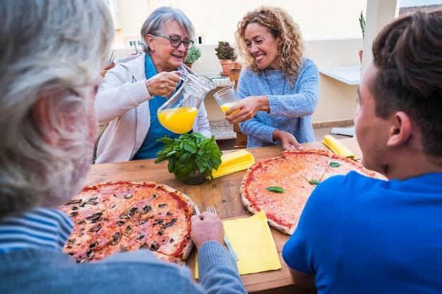 Grupo de pessoas ou família em mesa de madeira comendo pizza junto com duas grandes pizzas - dois idosos, uma mulher e um adolescente preparados para comer