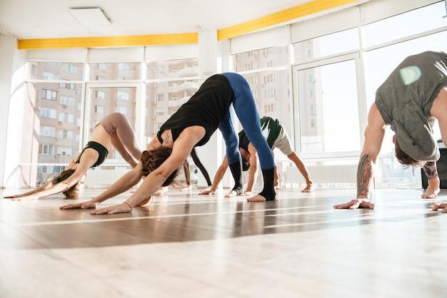 Grupo de pessoas praticando ioga em estúdio