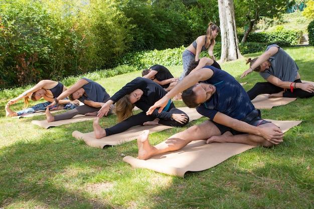 Grupo de pessoas praticando yoga e alongamento de corpos