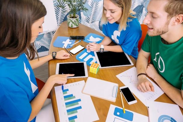 Grupo de pessoas que olham para tablet digital com ícones de mídia social no local de trabalho