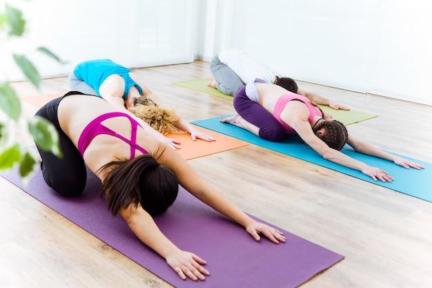 Grupo de pessoas que praticam yoga em casa. pose de balasana.