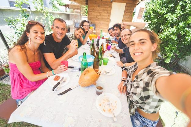 Grupo de pessoas que tomam selfie enquanto almoça ao ar livre