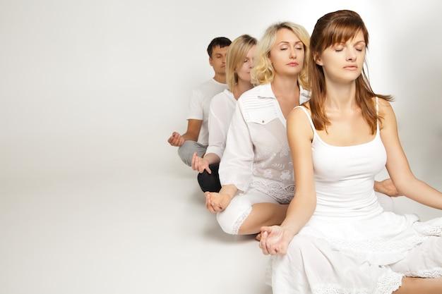 Grupo de pessoas relaxando e fazendo ioga em branco