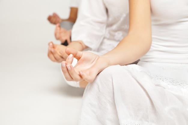 Grupo de pessoas relaxando e fazendo ioga em um estúdio branco