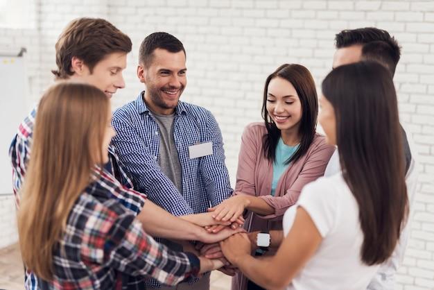 Grupo de pessoas reunidos em círculo e de mãos dadas.