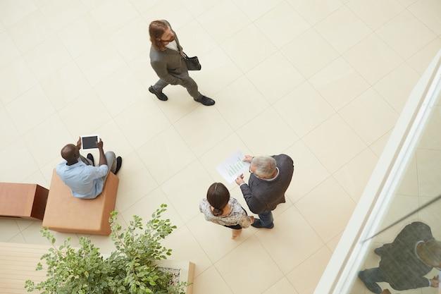 Grupo de pessoas reunidos em vista superior do lobby empresarial