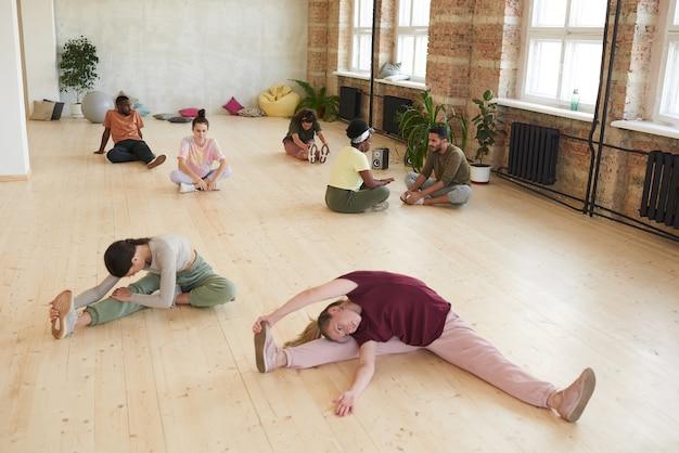 Grupo de pessoas saudáveis sentadas no chão e fazendo exercícios de alongamento durante o treinamento esportivo no health club