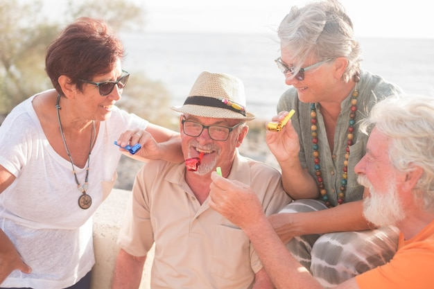 Grupo de pessoas se divertindo e comemorando algo que aconteceu - quatro idosos sorrindo e rindo na praia