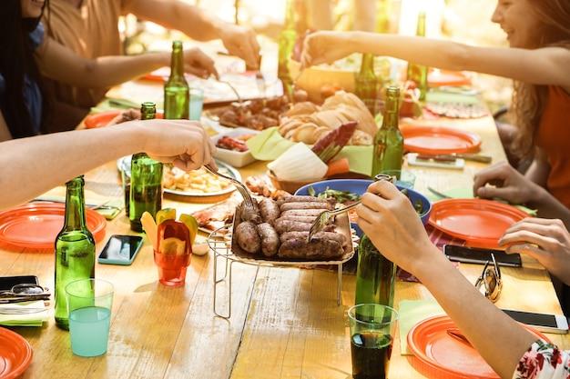 Grupo de pessoas se divertindo em uma festa de churrasco ao ar livre no terraço