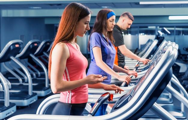 Grupo de pessoas se exercitando diligentemente na esteira da academia