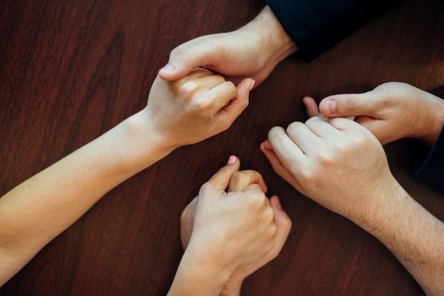Grupo de pessoas segurando as mãos uns dos outros