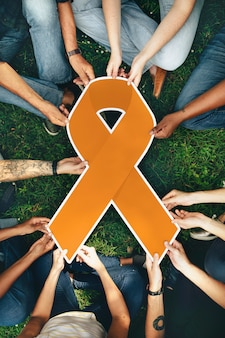 Grupo de pessoas segurando uma fita colorida laranja