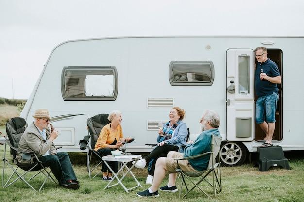Grupo de pessoas seniores se reunindo fora de um trailer