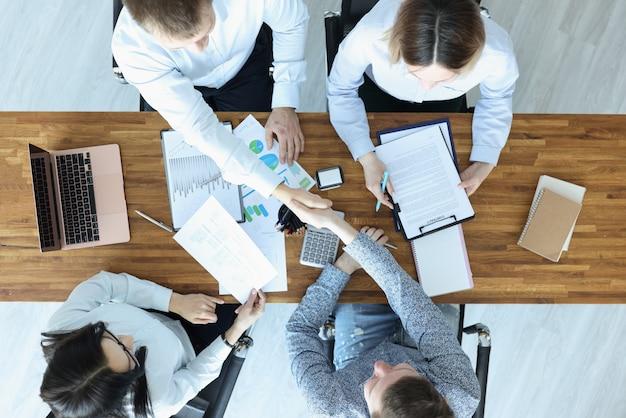 Grupo de pessoas sentadas à mesa e apertando as mãos vista superior. conceito de celebração de contratos