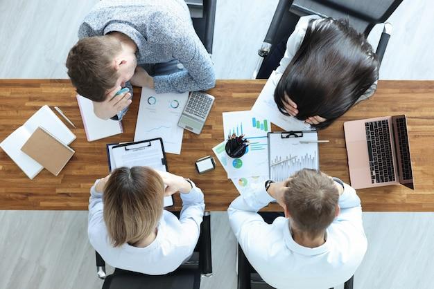 Grupo de pessoas sentadas à mesa e segurando a vista superior de suas cabeças. resolvendo problemas de negócios