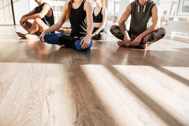 Grupo de pessoas sentadas com as pernas cruzadas no estúdio de yoga