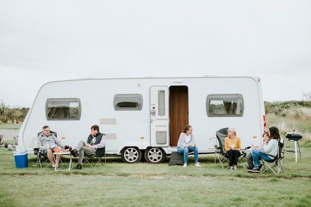 Grupo de pessoas sentadas do lado de fora de um estacionamento de trailers