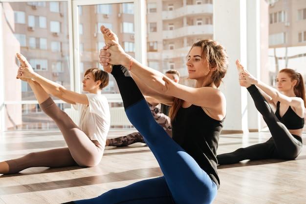 Grupo de pessoas sentadas e esticando as pernas no estúdio de yoga