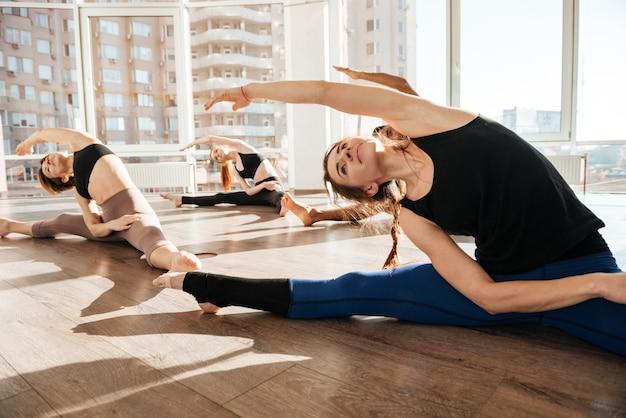 Grupo de pessoas sentadas e esticando no estúdio de yoga