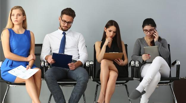 Grupo de pessoas sentadas em cadeiras durante a seleção de empregos