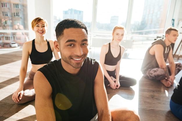 Grupo de pessoas sentadas no chão no estúdio de yoga