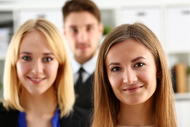 Grupo de pessoas sorridentes ficar no escritório olhando