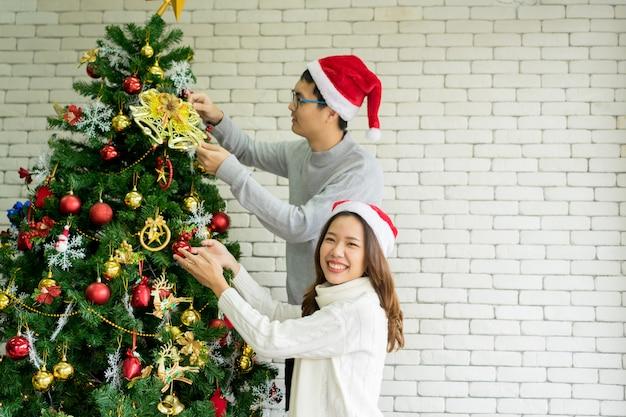 Grupo de pessoas sorrindo com sentimento de felicidade e segurando uma bola vermelha de enfeites para decorar na árvore do abeto na sala de estar