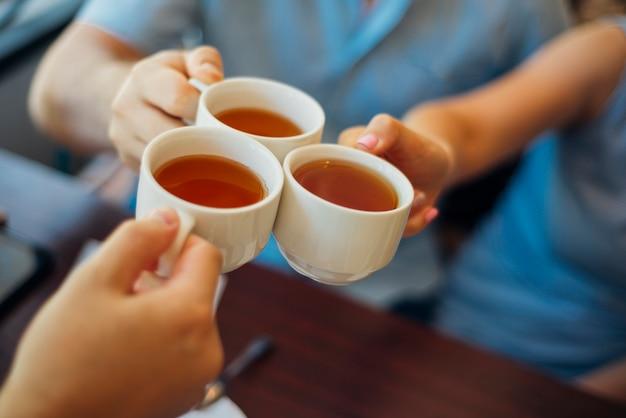 Grupo de pessoas tinindo copos com chá