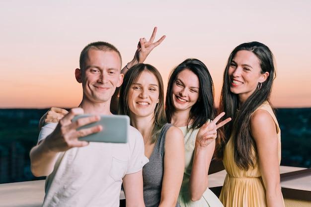 Grupo de pessoas tomando selfie na festa no terraço