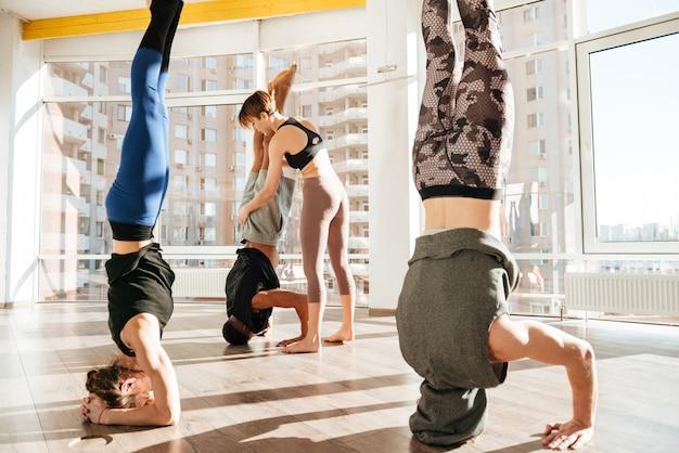 Grupo de pessoas trabalhando com instrutor e fazendo headstand
