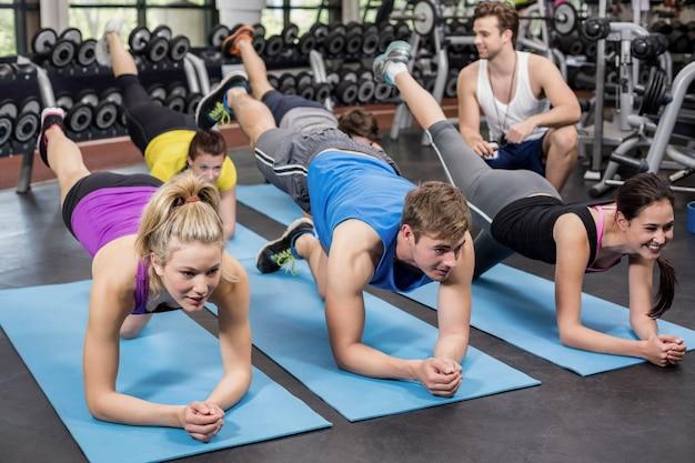 Grupo de pessoas trabalhando seus abs no ginásio