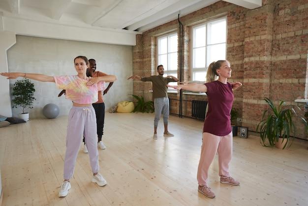 Grupo de pessoas treinando junto com o treinador durante as aulas de ginástica no ginásio