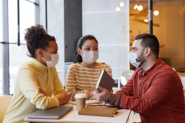 Grupo de pessoas usando máscaras enquanto trabalhavam na mesa de um café em reunião de negócios com medidas de segurança ambiciosas