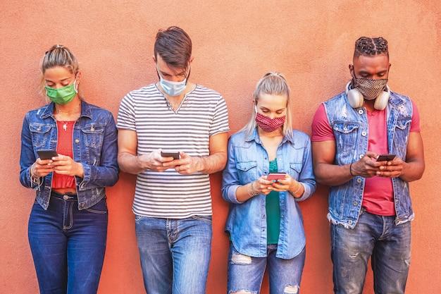 Grupo de pessoas usando seus smartphones de forma secreta 19 vezes protegidas com máscara facial - amigos checando notícias online enquanto ficam de pé junto à parede segurando celulares