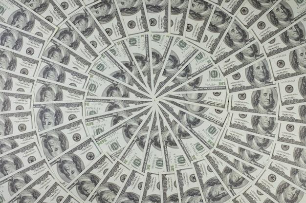 Grupo de pilha de dinheiro com notas de 100 dólares americanos, muitas delas dispostas em um lindo círculo