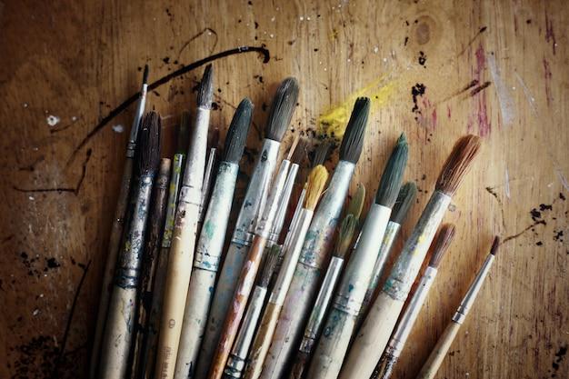 Grupo de pincéis de pintura usados velhos em uma tabela de madeira rústica. formato horizontal.