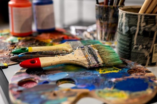 Grupo de pincéis e paletas de potes de guache no local de trabalho do pintor moderno